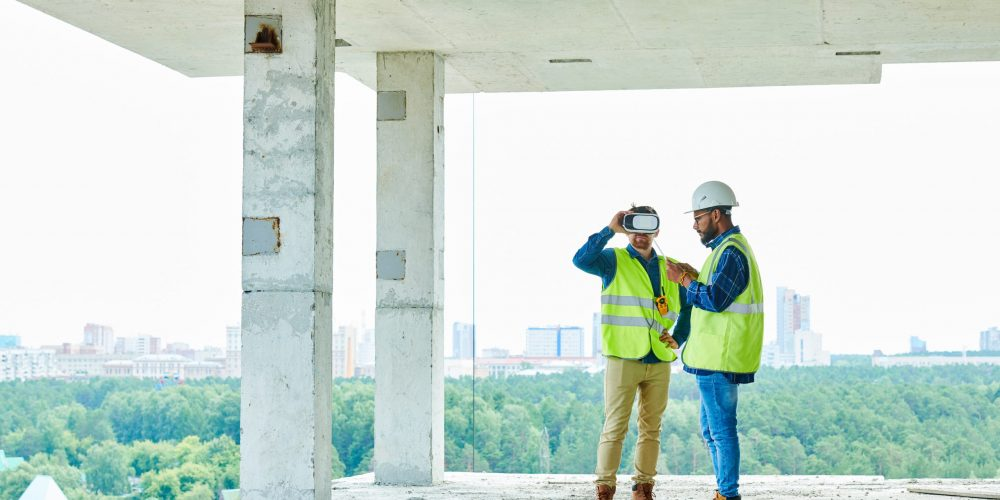 Full length portrait of two contemporary workers using VR to visualize projects standing in unfinished building on construction site, copy space